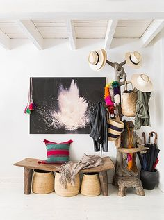"""Hats and bags from Jenni's online textiles shop,Intiearth, hang on a carved coatrack besides a photograph by Hans Gissinger in the entryway. """"We don't wear shoes in the house, so everybody has a basket they put their shoes in."""""""
