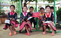 Books are a girl's best accessory. These girls from Vietnam wear traditional dresses made by their mothers to school every day.