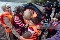 Migrants and refugees arrive on Kagia beach near the village of Sykamia, west of the port of Mytilene, on the Greek island of Lesbos after crossing the Aegean sea from Turkey on September 23, 2015. EU ministers neared a compromise on plans to relocate 120,000 refugees at emergency talks despite deep divisions over how to handle Europe's worst migration crisis since World War II. AFP PHOTO / IAKOVOS HATZISTAVROU