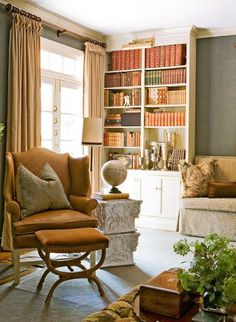 """the Hues have """"It!""""  A complete overhaul of this 1970s-style home by designers Roger Higgins and Ann Shipp included the addition of pale-blue ceilings, antique-white trim, and rich bronze hues in every room. Framed by organic mohair-covered walls, a bookcase lined with autumn-hued volumes echoes the home's chosen color palette. A lower shelf displays a collection of vintage trophies that offer a whimsical touch of history."""
