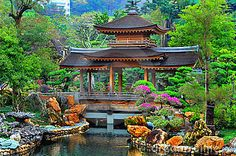 pagoda in front of a pond in a beautiful chinese garden surrounded with exotic colors of spring foliage. location is nan lian gardens located at diamond hill, hong  kong.