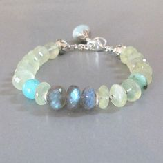 Faceted icy pale green Prehnite rondelles glowing as if struck by sunlight are alternated with tiny faceted fine silver beads. They surround a trio of