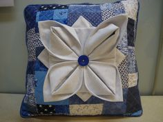 This pillow has a pieced background with a folded fabric flower on top.  It is 3-D