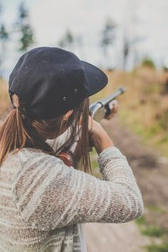 Country girl shooting a shotgun