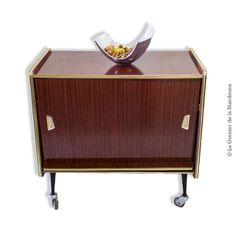 Meuble bar télévision vintage sur roulettes. Façade rotative fermant à clef, ouvrant sur un aménagement de bar, avec 2 plateaux pour verres et bouteilles.
