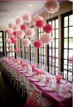 Pretty table setting with hanging pom poms in various shades of pink.