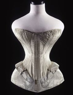 Blue silk corset. A pale blue silk corset, with whalebone used throughout to shape the corset. Two shallow basques are applied at hip level either side of the busks and continue upwards and over the hips to the back; three buttons, covered in the same silk, are sewn in vertical rows on each side of the basques, front and back. It was made especially for display purposes at the Great Exhibition.