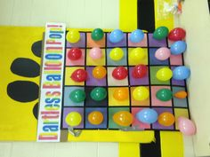 Made out of a large piece of cardboard with construction paper squares taped off in a grid. Hot glue thumb tacks to each square behind the balloons and throw beanbags instead of darts. Was a huge hit at the school carnival!