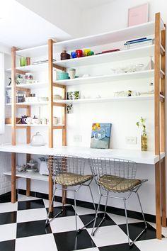 Cocina con piso tipo damero. Mueble de guardado y comedor diario en laca blanca y lenga con lustre mate. Sillas bertoia.