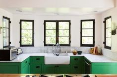 Kelly green kitchen cabinets with casement black frame windows and farm sink.  Marble countertops.  No upper kitchen cabinets.