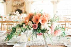 An array of light orange lilies, pink peonies and flowing greenery in crystal bowls for Shannon and Brian's romantic and rustic Audubon wedding - by Buttercup: Lauren Fair Photography.