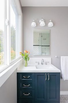 Contemporary bathroom features a navy washstand topped with white quartz placed under a frameless mirror illuminated by a three light sconce.