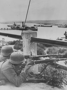 Two German soldiers in position against the background of the harbor in Lithuania.