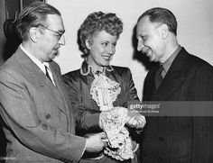 Actress Irene Dunne congratulates authors Howard Lindsey (L) and Russel Crouse (R) for receiving the Pulitzer Prize for their play, 'State of the Union,' Hollywood, California, May 6, 1946. Dunne is starring in the film, 'Life With Father,' based on the play by the two authors.