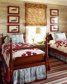 Limed walls, bamboo roman shade, red and white quilt with contrast shams and bedskirts, red framed duck prints, striped rug, antique beds