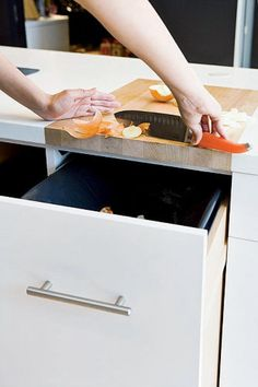 These trash bins pull all the way out of their cabinets, so that you can take them anywhere in the kitchen. There's also a wood cutting board built right on top, so that you can chop veggies and scoop the trash right into the bins.