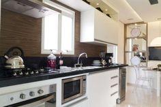 Cozinha bancada preta e parede madeira