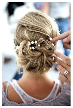A few flowers give this updo the final touch | Unas flores adornan este precioso peinado recogido de novia