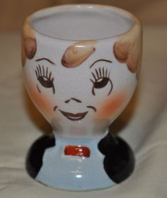 Now he's going solo. Face egg cup showing a well mannered person with hair curls around his face and bright rosy cheeks.