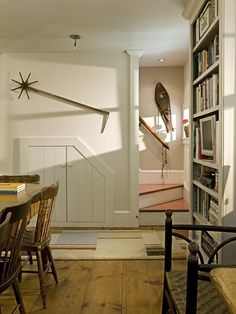 The underside of this staircase serves as storage for both the kitchen and the powder room on the other side of the stairs. An old timber measurer, and wooden snowshoe provide warm, artistic decoration to the light walls. The mast from a sailboat the client used as a child finds new life being repurposed as a stair railing. Renovation/Addition. Rob Karosis Photography