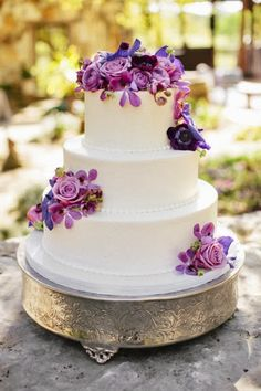 charming three-tiered confection with purple blooms by Polkadots Cake