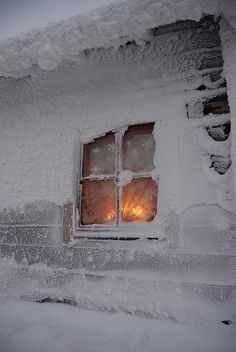 Cozy warmth radiating from the snow covered window....