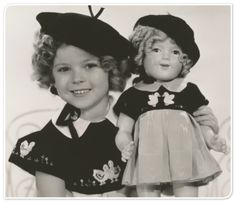 "The dress worn by Shirley Temple in this photo, from the 1935 film ""Curly Top,"" is in the auction; opening bid is $3,000. The doll she's holding is also in the auction; the current high bid is at $1,400."