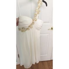 Off-white/gold GORGEOUS Prom Dress Beautiful gown. Off-white colored dress w/ gold flower one sided strap. Size 4. Worn once, dress is in new condition. Great for formal events and prom. Short/Mid-length. Zipper on the back. Any more details let me know! Xscape Dresses Prom