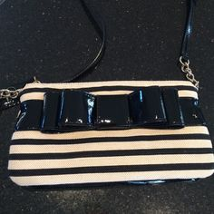 NWT Kate Spade Crossbody Bag. Black and cream stripe canvas with black patent leather trim. Big bow in front. Strap is adjustable. Strap has a small section of gold chain. Inside has pink lining. Two open pockets and a zipper pocket. kate spade Bags Crossbody Bags