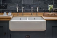 A double Belfast farmhouse sink with four bibcock taps sit within oak shaker cabinets painted with Farrow & Ball Down Pipe. Rustic metal door knobs match the darkness of the slate tiles which sit perfectly above the oak worktop.
