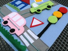 This busy / quiet book page made of felt uses strings to move Little felt cars through the crossroads. There are the main street signs and lights as