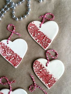A set of three white ceramic heart Christmas ornaments that can be used as Christmas tree decoration or gift tags.  The heart is made of white