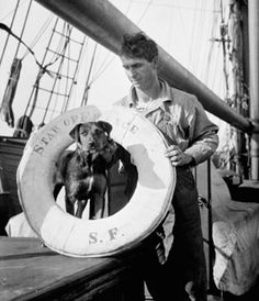 Man standing with his dog on the deck of a sailing ship. San Francisco