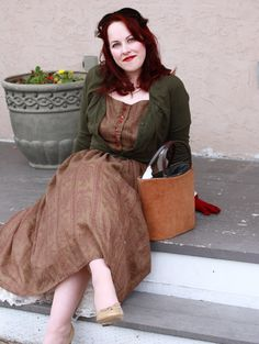 Reclining in an outfit comprised of earthy hues. Love the dark red gloves.
