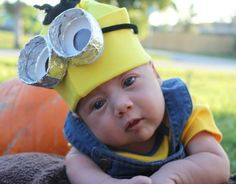 """DIY baby minion costume. Yellow ski cap. Black pipe cleaners as hair. 2 cardboard strips cut into 2"""" and wrapped in tin foil for glasses. White poster board to cut into circles for eyes."""