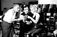 Marilyn Monroe on the set of Let's Make Love with George Cukor and Yves Montand.