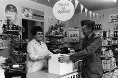 Värmland Eda kommun Åmotfors 1971 Lantbrevbäraren Sigurd Nilsson i Åmotsfors i Eda kommun, Värmland hämtar varor hos Randi Andersson som tillsammans med sin make driver en livsmedelsaffär i Djupfors. Det är den enda livsmedelsaffären på en halvmils omkrets.