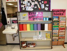 """Our freedraw shelf. With broken pencil cup and sharpened pencil cup. Different sizes of paper, extra crayons, small white baskets have (bookmark paper, squares for our mini museum, and oops to fix...based on the book """"A Beautiful Oops."""" Bottom shelf has bins for broken crayons and peeled crayons."""