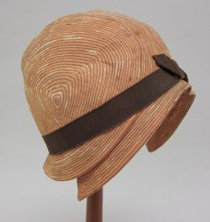 Beige silk cloche | United States, 1923 | Domed crown made of beige silk top-stitched and quilted to a base of grayish felt. The stitching is in the form of repeated and spiraling lines. At base of crown is a wide band of brown grosgrain ribbon with bow at front | The brim turns downward | University of North Texas