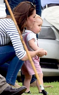 June 15, 2014 Catherine Duchess of Cambridge and Mum of 10 month old Prince George has a firm grip on him as he takes his first steps on the Cirencester Park as his Dad and Uncle Harry played polo on the field.
