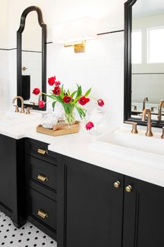 This bathroom space uses a classic black-and-white design for a clean look that always feels sharp and connected. The brass sconce and fixtures are a current-day update to the chrome and silver that have dominated the market in past years. Drawers under the double vanity hold essential bathroom items, and an angular brass tray between the sinks displays flowers in simple crystal vases.