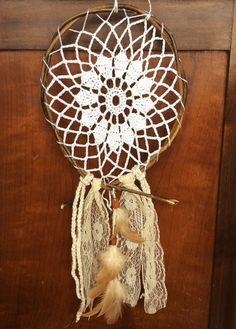 Filtro de sonhos em crochê com acabamento em galhos secos, adornado com rendas e penas.