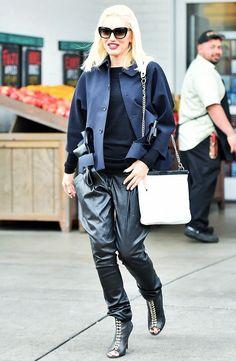 Gwen Stefani wears a cutout bow jacket by Comme Des Garçons, leather pants, chain-strap shoulder bag, and peep-toe boots