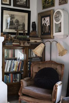 Cozy reading nook. Velvet chair and vintage wood bookcase.