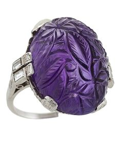 An Art Deco platinum ring with amethyst and diamonds. The ring has a carved cabochon amethyst with an approximate total weight of 36.50 carats, and 6 baguette diamonds with an approximate total weight of .64 carats. The amethyst is carved in a stylised foliate motif, held in place by 8 stylised engraved art deco patterns. The gallery displays an elaborate scroll motif on top of a set row of rose-cut diamonds. The top of the shank contains the vertically-set baguette diamonds. Circa 1920s.