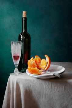 """Deep Blue and Orange - <a href=""""http://nikolay-panov.pixels.com/products/deep-blue-and-orange-nikolay-panov-art-print.html"""">nikolay-panov.pix...</a> Fruit classic still life photography with glass of red wine, tall bottle, and sweet orange pulp and slices on the table covered by drapery on dark blue background"""