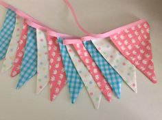 Pretty pastel bunting featuring dots, checks and a super cute elephant fabric. All flags are double sided. Great for a bedroom bunting, a nursery, baby shower, birthday party for young or old.  Flags are approx 5.25 inches wide by 7.25 inches long measuring 2.5m or 98 including 12inches at each end for ties.  Flags are machine washable at low temperatures, they are not toys and should be hung out of the reach of small children.