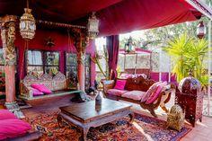 décoration orientale à la terrasse : tapis kilim, table basse en bois, balançoire suspendue et coussins roses