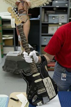 """ONE OF KURT COBAIN'S GUITARS, WITH A STICKER THAT READS """"VANDALISM: BEAUTIFUL AS A ROCK IN A COP'S FACE."""""""