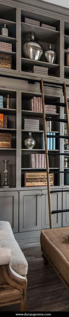 Shabby chic styled gray and distressed painted library cabinets and built-in bookcases in Heritage Paint from Dura Supreme Cabinetry with rolling ladder and burlap inspired furniture. Home Office with Shabby Chic Style. Design by Lindsey Markel of Dillman & Upton